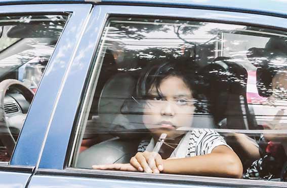 niño triste en auto